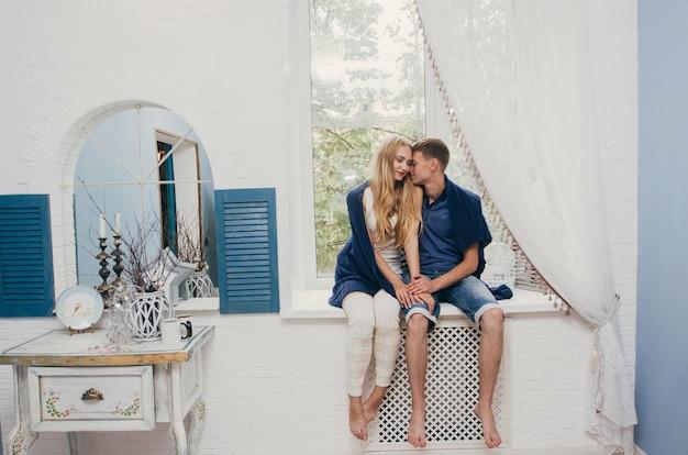 Paar verliefd om thuis te zitten op het raam. tedere liefdevolle omhelzing van pasgetrouwden. leuke ochtend gelukkige stemming van een liefdevol paar. vrouw knuffelt tot vriendje romantische gevoelens. valentijnsdag