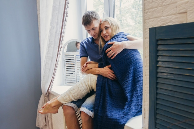 Paar verliefd om thuis te zitten op het raam. tedere liefdevolle omhelzing van pasgetrouwden. leuke ochtend gelukkige stemming van een liefdevol stel. meisje knuffelt tot vriendje romantische gevoelens. valentijnsdag