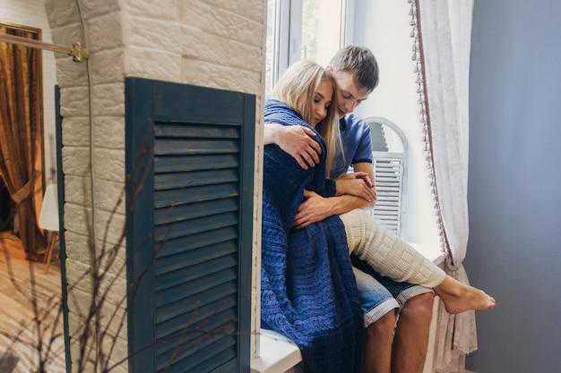 Paar verliefd om thuis te zitten op het raam.