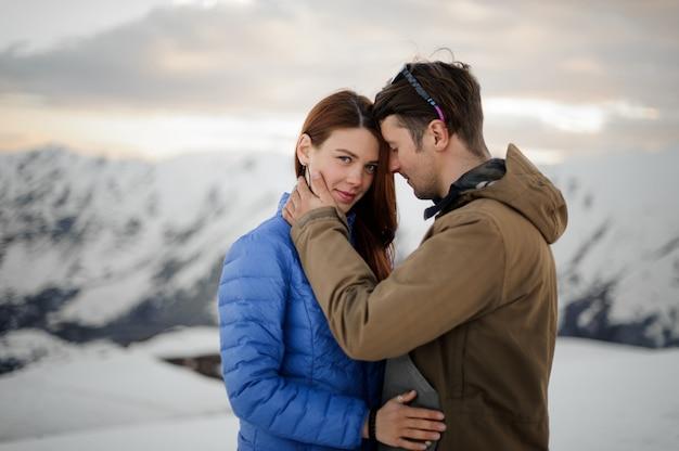 Paar verliefd op de winter zachtjes omarmen in de bergen