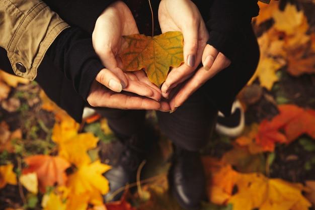 Paar verliefd op open handen met een geel blad in het bos.
