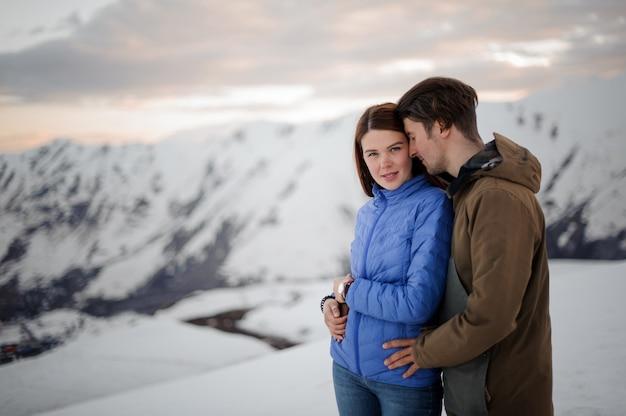 Paar verliefd op winter zachtjes omarmen in prachtige bergen