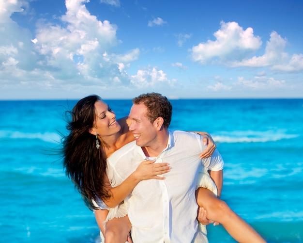 Paar verliefd piggyback spelen in het strand