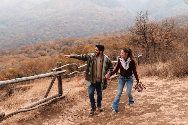 Paar verliefd wandelen in de natuur in de herfst en hand in hand.