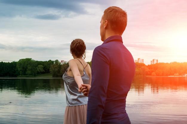 Paar verliefd wandelen langs de waterkant met haar hond.