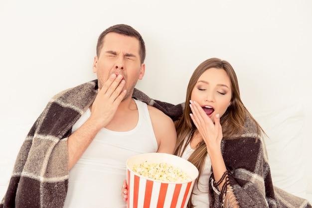 Paar verliefd zitten met popcorn en geeuwen tijdens het kijken naar film