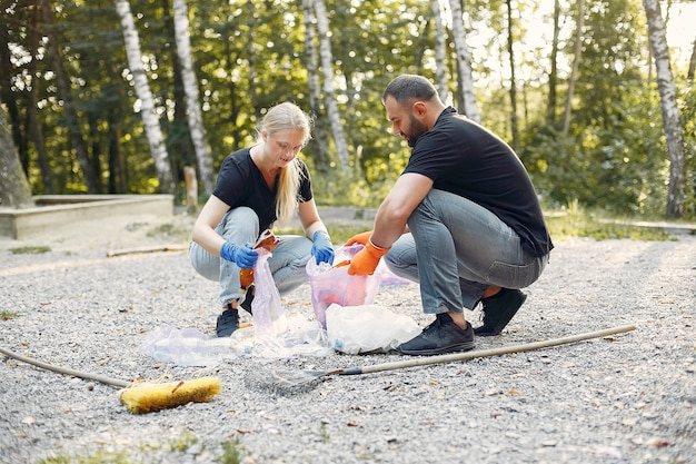 Paar verzamelt afval in vuilniszakken in park