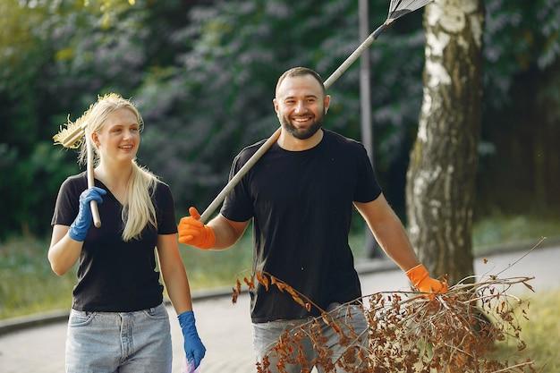 Paar verzamelt bladeren en maakt het park schoon