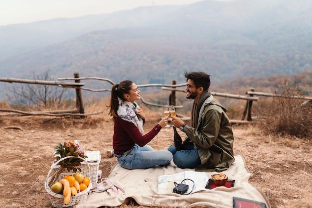 Paar vieren verjaardag op picknick. paarzitting op deken en het toejuichen met wijn. herfst tijd.