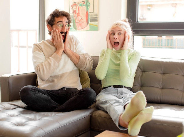 Paar voelt zich gelukkig, opgewonden en verrast, vrouw kijkt opzij met beide handen op het gezicht