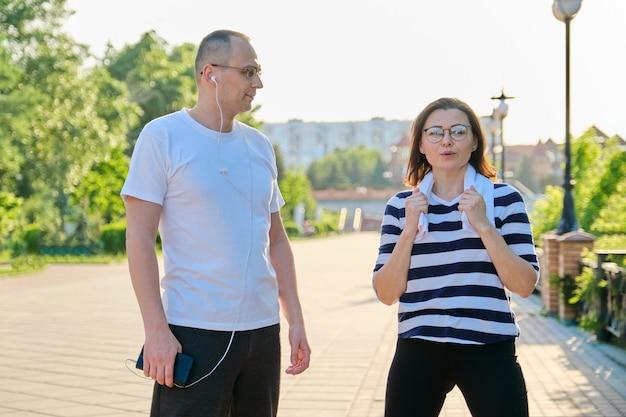 Paar volwassen mensen rusten praten na sportoefeningen, joggen in het park. actieve gezonde levensstijl, sport, fitness bij mensen van middelbare leeftijd