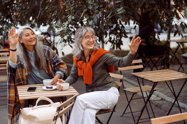 Paar volwassen vrouwenvrienden zwaaien met de hand en bellen ober in straatcafé