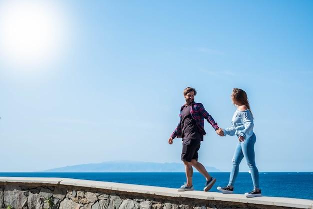 Paar volwassenen die samen lopen en hun handen nemen met de oceaan of de zee en de prachtige eilandachtergrond - gelukkige vakanties samen - man lachen en kijken naar zijn vriendinnen of vriend