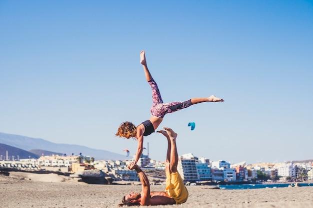 Paar volwassenen in een vriendschap die sporten en activiteiten doen zoals acroyoga op het strand op het zand met de bergen op de achtergrond