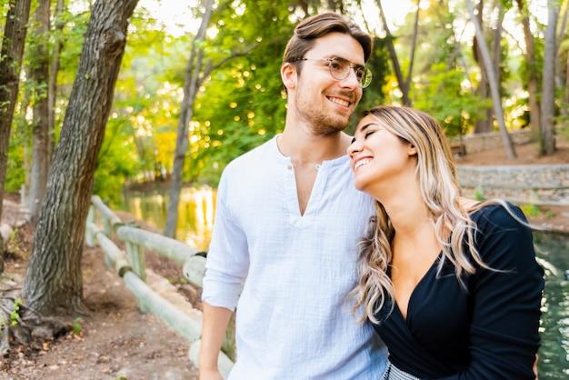 Paar vrienden flirten plezier tijdens het knuffelen op een wandeling in een natuurpark.