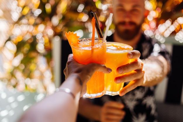 Paar vrienden rammelende glazen smakelijke tropische cocktails op zonnige dag in café