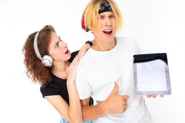 Paar vrolijke studenten op een witte achtergrond in hoofdtelefoons met een tablet in hun handen met gebaar als