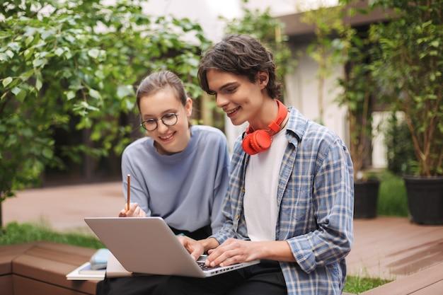 Paar vrolijke studenten zittend op een bankje en bezig met laptop op de binnenplaats van de universiteit. jonge man en dame studeren samen buitenshuis