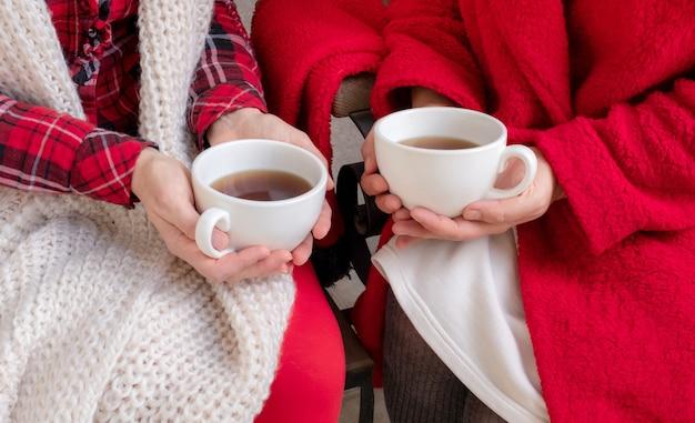 Paar vrouw vrouwelijke bedrijf koffie thee beker rode feestelijke kleren kerstmis nieuwjaar valentijn