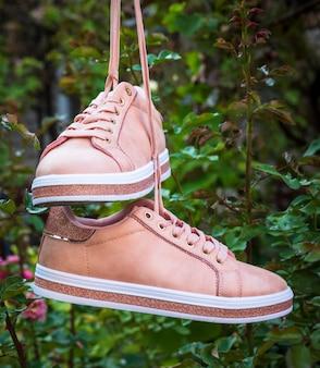 Paar vrouwelijke leer roze schoenen die op een koord hangen