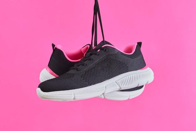 Paar vrouwelijke sportsneakers voor hardlopen en fitness, hangend aan schoenveters op roze achtergrond