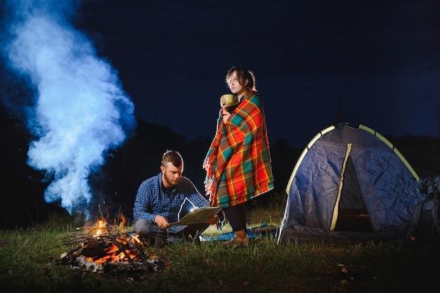 Paar wandelaars genieten van elkaar, staan 's nachts bij kampvuur onder avondlucht in de buurt van bomen en tent
