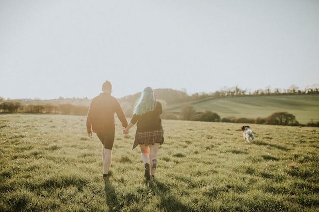 Paar wandelen en hand in hand buitenshuis