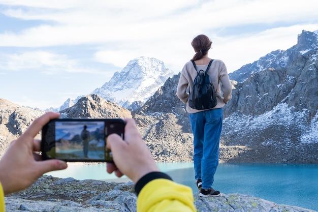 Paar wandelen op de berg op herfstdag man die foto neemt op de telefoon van zijn vriendin
