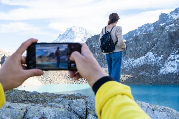 Paar wandelen op de berg op herfstdag. man die foto neemt op de telefoon van zijn vriendin.