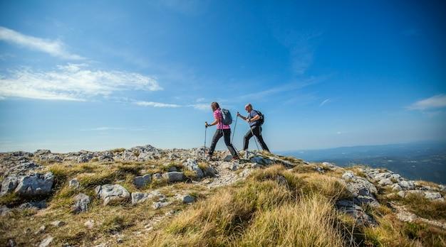 Paar wandelen op nanos plateau in sloveniã «tegen een blauwe hemel