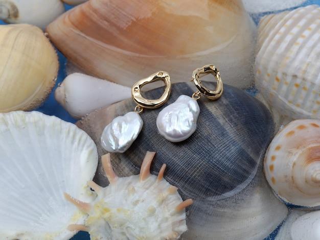 Paar witte barokke parel gouden oorbellen op mariene schelp achtergrond
