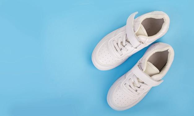 Paar witte leren sneakers geïsoleerd op blauwe ondergrond