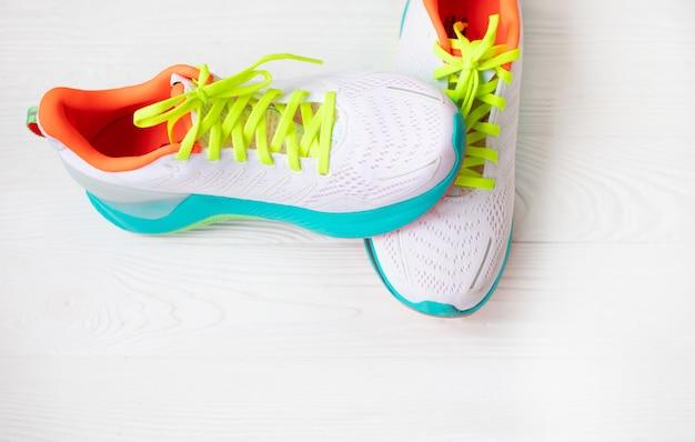 Paar witte sneakers op houten achtergrond
