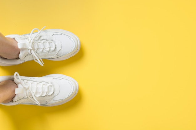 Paar witte vrouwelijke sneakers op geel. plat leggen, bovenaanzicht minimaal.