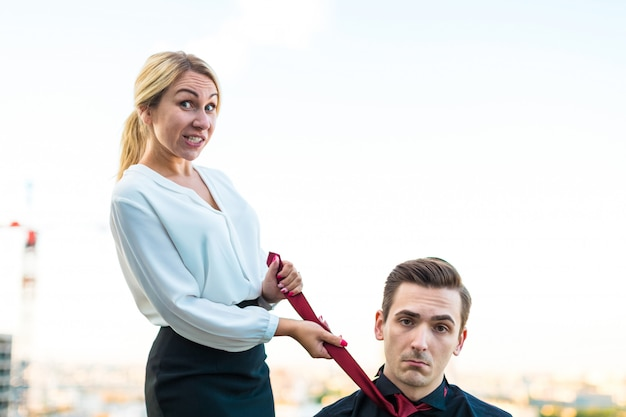 Paar zakenlieden, aantrekkelijke brunette man en mooie blonde vrouw staan op het dak, meisje trekt man's das