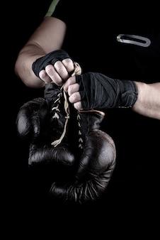 Paar zeer oude bokssporthandschoenen in handen van mannen