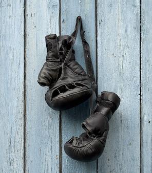 Paar zeer oude leer zwarte bokshandschoenen die op een spijker hangen