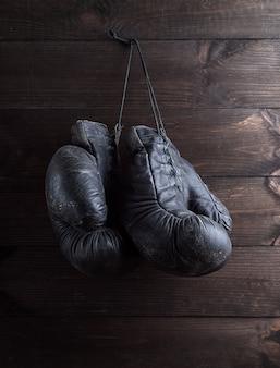 Paar zeer oude sjofele zwarte leer bokshandschoenen die op spijker hangen