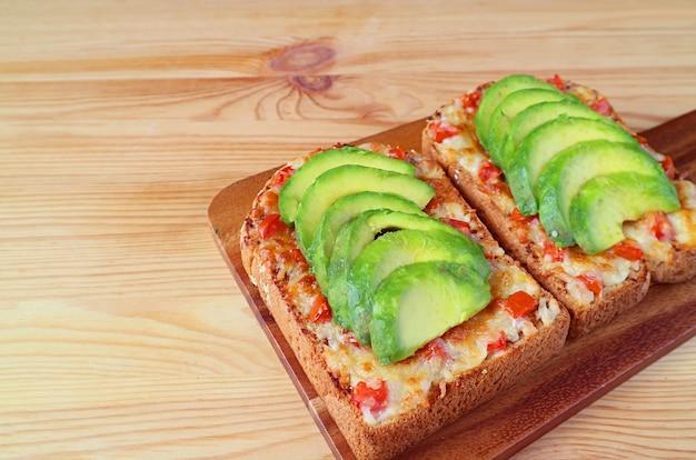 Paar zelfgemaakte gegrilde kaas toast gegarneerd met tomaat en gesneden avocado op houten tafel