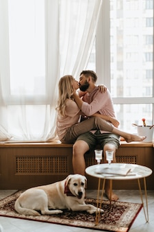Paar zit op vensterbank en kussen. meisje in beige outfit knuffelen man terwijl hun labrador op tapijt ligt.