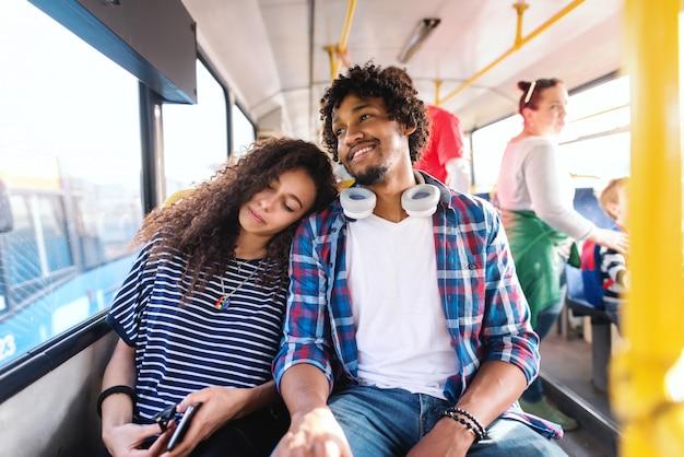 Paar zitten en rijden in de stadsbus. meisje slapen en leunend hoofd op de schouder van haar vriendje.