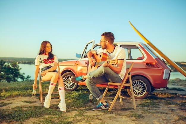 Paar zitten en rusten op het strand gitaar spelen op een zomerdag in de buurt van de rivier