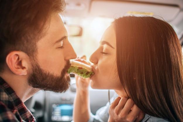 Paar zitten in de auto en het eten van een sandwich van beide kanten ervan