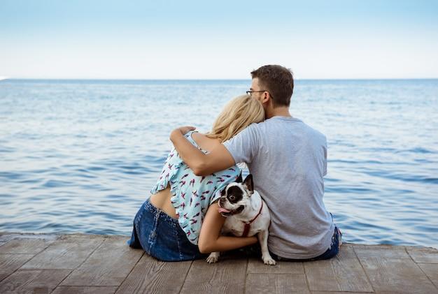 Paar zitten met franse bulldog in de buurt van de zee