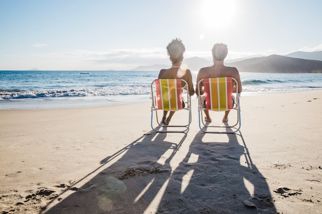 Paar zitten op het strand vormen schaduwen