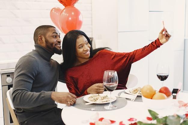 Paar zittend aan tafel, eten, foto nemen en lachen op valentijnsdag