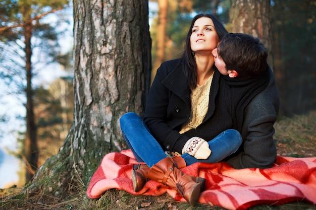 Paar zittend naast een boom in het bos