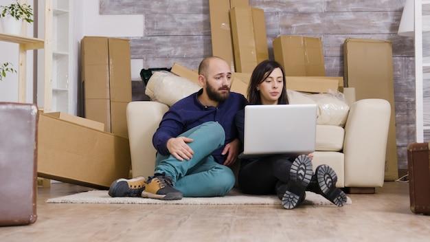 Paar zittend op de vloer van nieuw appartement en laptop gebruiken voor online winkelen.