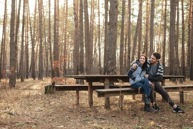 Paar zittend op een bankje in het bos