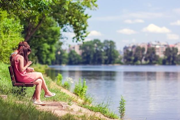 Paar zittend op een bankje naast een meer op een zonnige zomerdag